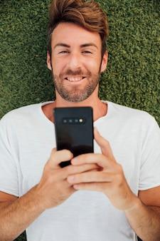 Vista superior homem barbudo segurando o telefone