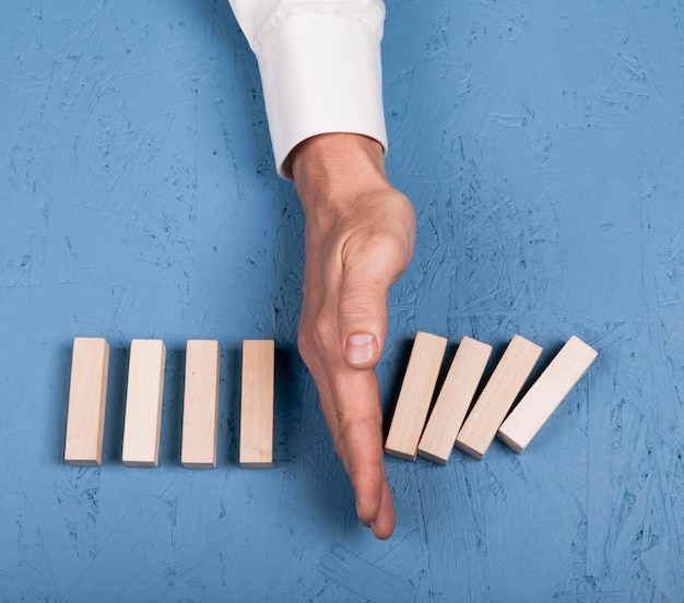Vista superior homem bloqueando pedaços de madeira de cair