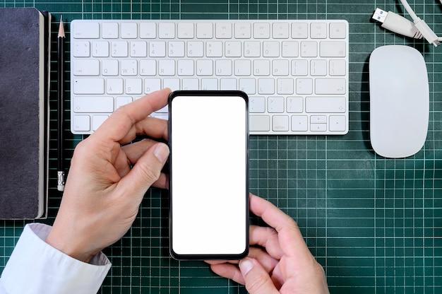 Vista superior homem e segurando o smartphone com tela em branco.