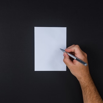 Vista superior homem escrevendo no papel com caneta em fundo preto.