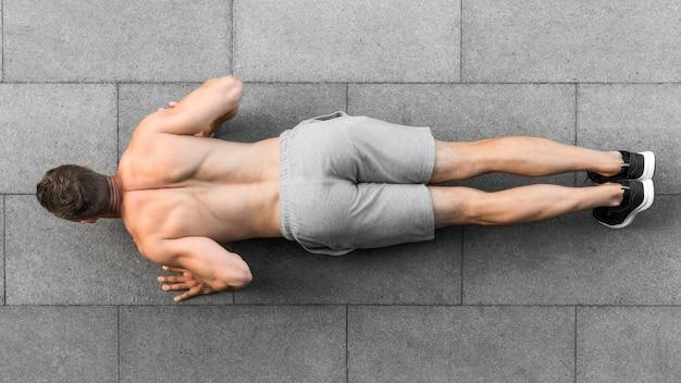 Vista superior homem fazendo flexões