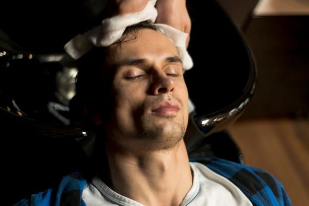 Vista superior homem recebendo seu cabelo lavado
