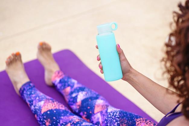 Vista superior horizontal de uma mulher irreconhecível vestida com uma roupa de ioga, segurando uma garrafa de água fresca. estilo de vida de hidratação e fitness. exercício e hábitos esportivos saudáveis no verão.
