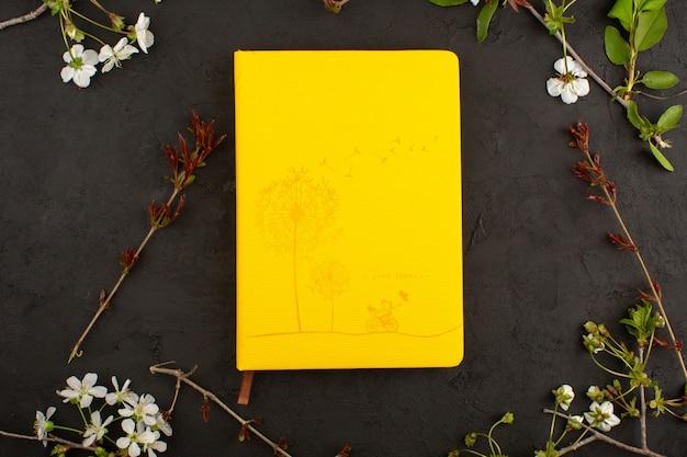 Vista superior, imagem amarela, juntamente com flores no chão escuro