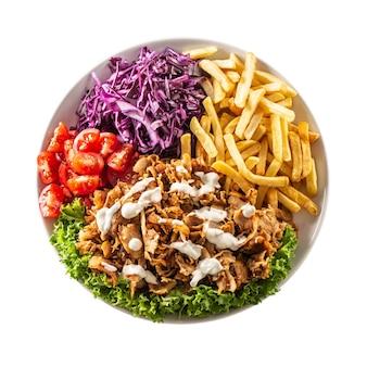 Vista superior isolada tradicional espetada de frango turca preparada com lindas batatas fritas, legumes frescos e molho saboroso.