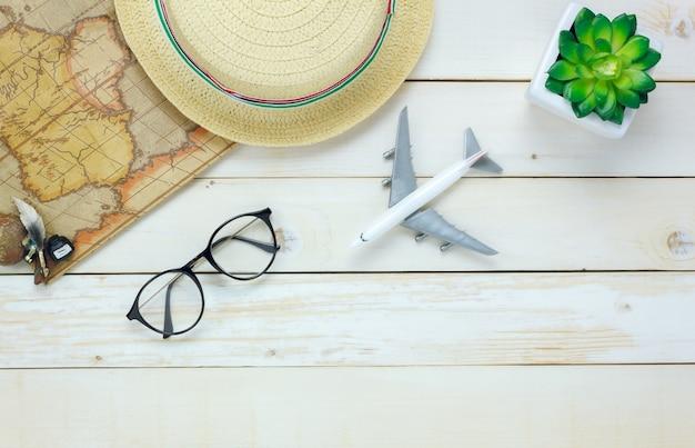 Vista superior itens de viagem essenciais em fundo de madeira branca com espaço de cópia.