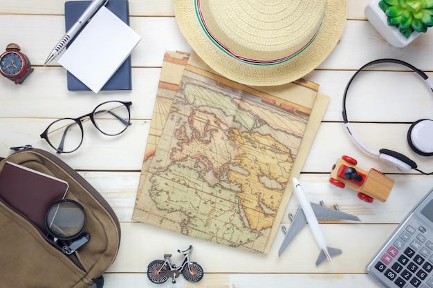 Vista superior itens de viagem essenciais. o saco da calculadora, caderno, árvore, mapa, passaporte, avião, auscultadores, música, óculos, branca, madeira, fundo.