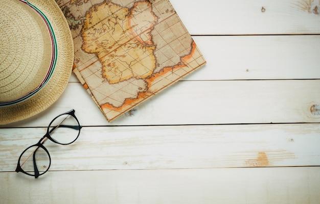 Vista superior itens de viagem essenciais. os óculos do homem do chapéu do passaporte do mapa no fundo de madeira branca com espaço da cópia.