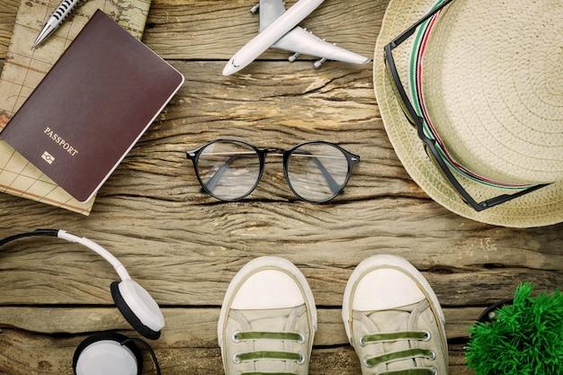 Vista superior itens de viagem essenciais. os sapatos do caderno de árvore traz passaporte de óculos de carro de avião em fundo de madeira rústica.