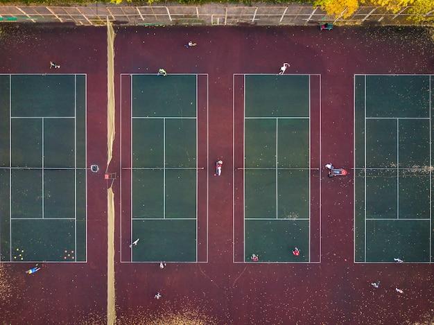 Vista superior jogar tênis em vários tribunais zangão aéreo baleado