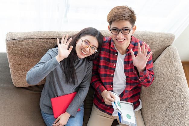 Vista superior, jovem mulher bonita e namorado bonito usando óculos e sentado lendo livros