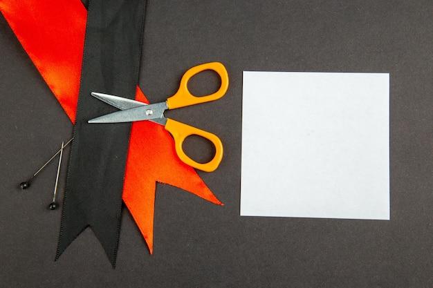 Vista superior laço preto com laço vermelho e tesoura em fundo escuro