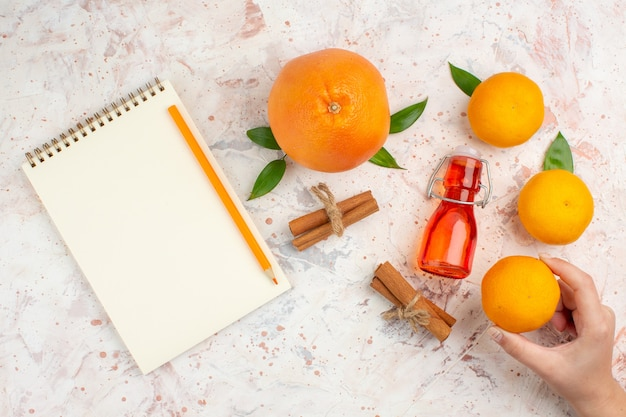 Vista superior laranja fresca canela paus de tangerina na mão feminina, um lápis, um caderno na superfície brilhante