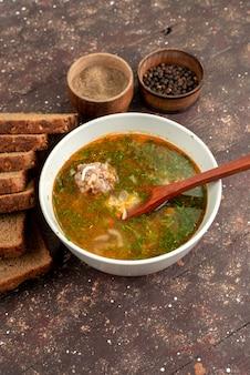 Vista superior laranja sopa de legumes com pão loafs verdes e alho em marrom, comida refeição sopa pão