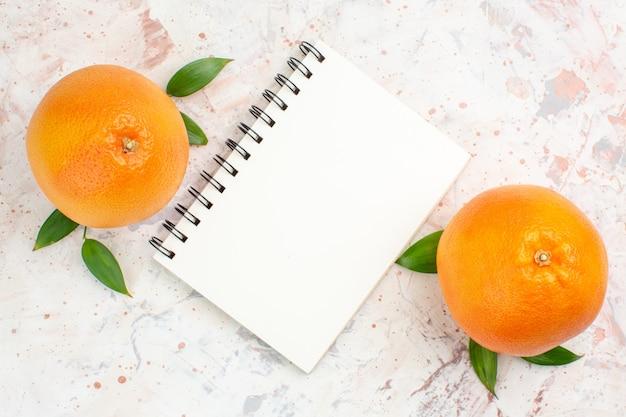 Vista superior laranjas frescas um caderno em superfície brilhante isolada