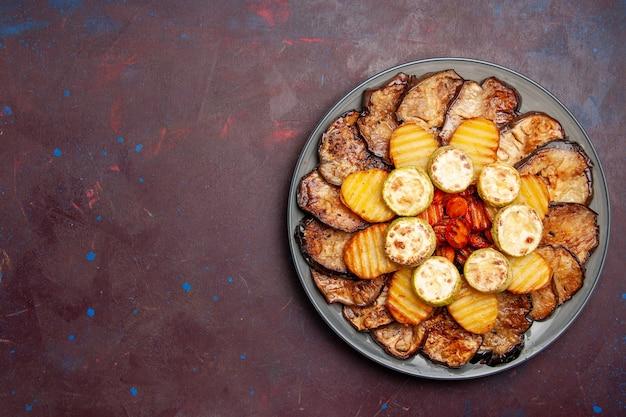 Vista superior, legumes assados, batatas e berinjelas recém-saídas do forno em um espaço escuro