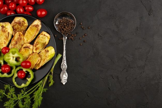 Vista superior, legumes cozidos e fatiados, como pimentão verde e tomate cereja vermelho de berinjela, dentro da placa preta no escuro