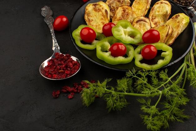 Vista superior legumes fatiados e todo dentro de chapa preta, juntamente com verduras no fundo escuro