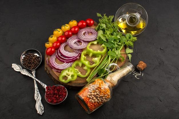 Vista superior legumes frescos coloridos fatiados e inteiros, como cebola fatiada pimentão verde tomate amarelo e vermelho na mesa marrom e escuro