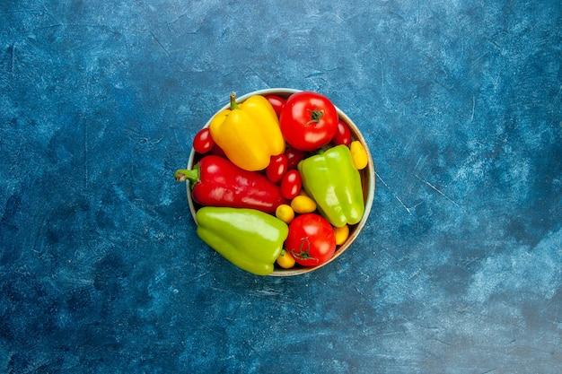 Vista superior legumes frescos cores diferentes pimentões tomates tomate cereja em uma tigela na mesa azul com espaço de cópia