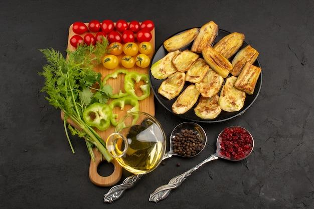 Vista superior legumes frescos fatiados e inteiros, juntamente com azeite de oliva no fundo cinza