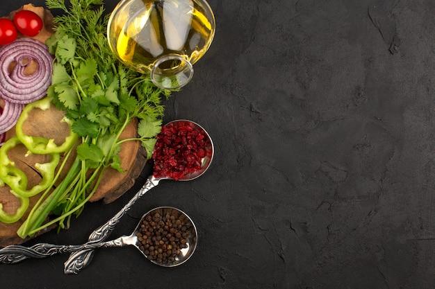 Vista superior legumes frescos fatiados e inteiros, juntamente com azeite no chão escuro