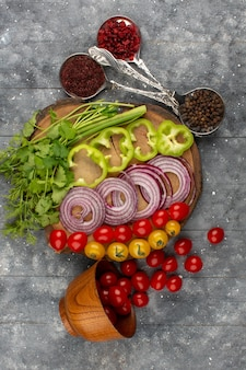 Vista superior legumes frescos fatiados inteiros, como cebolas verdes tomates no cinza