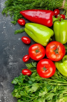 Vista superior legumes frescos pimentões vermelhos e verdes tomates cereja salsa tomates em superfície escura