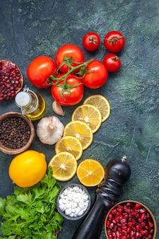 Vista superior legumes frescos tomates fatias de limão sal marinho em uma tigela pequena moedor de pimenta na mesa da cozinha
