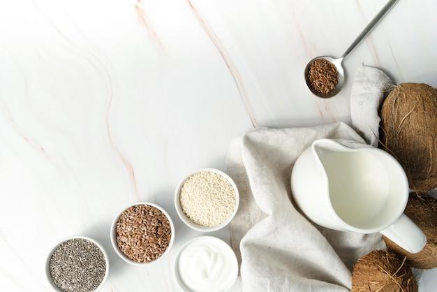 Vista superior, leite de coco e sementes copiam o espaço