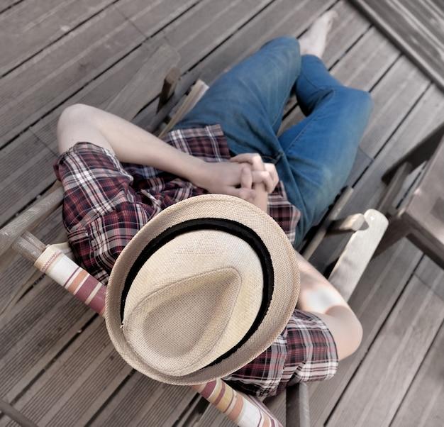 Vista superior, ligado, um, homem jovem, com, chapéu, relaxante, ligado, um, cadeira lounge, ligado, madeira, terraço