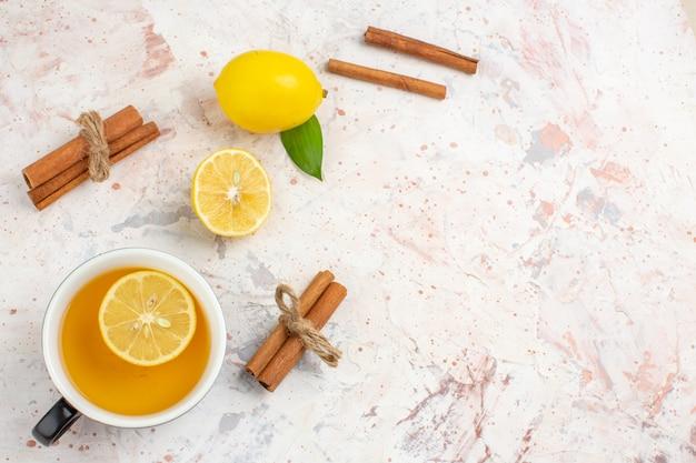 Vista superior limão fresco cortado limão canela varas uma xícara de chá de limão em uma superfície isolada brilhante espaço livre