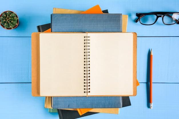 Vista superior livro maquete e lápis nota na mesa de madeira azul