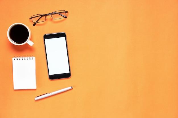 Vista superior, local de trabalho moderno com notbook e caneta com telefone inteligente colocado no fundo laranja. espaço de cópia adequado para uso em gráficos.