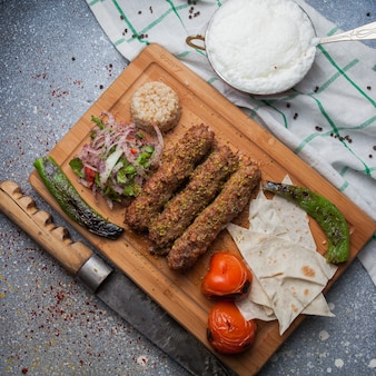 Vista superior lula kabab com legumes fritos e cebola picada e faca e ayran na tábua
