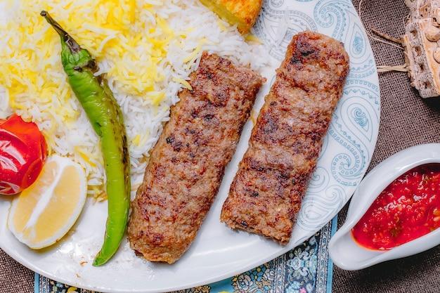Vista superior lula kebab com arroz e legumes com uma fatia de limão