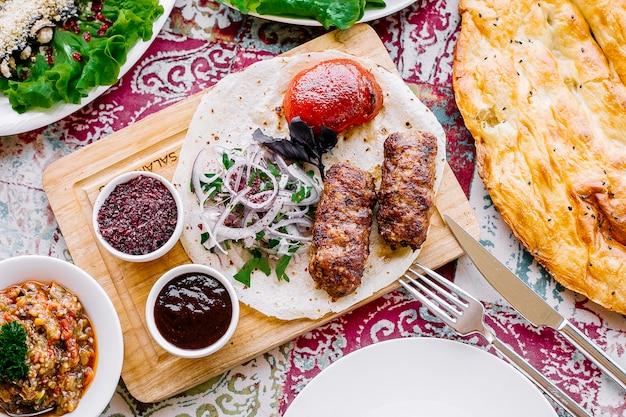Vista superior lula kebab no pão pita com cebola tomate e molhos no quadro