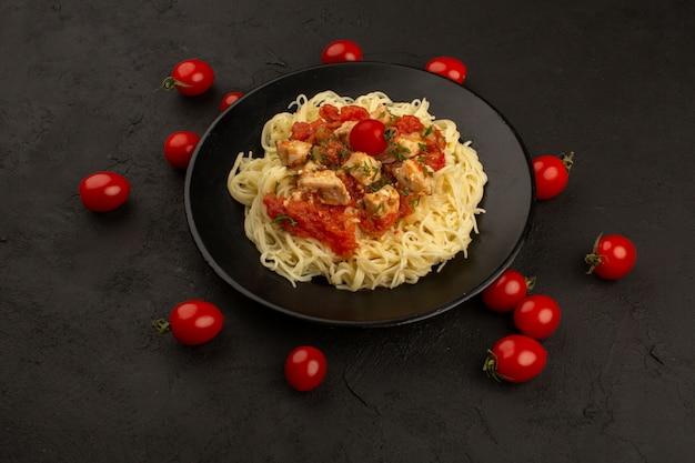 Vista superior, macarrão cozido, com, molho, dentro, prato preto, ao redor, vermelho, tomate cereja, chão escuro