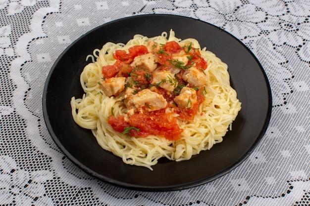 Vista superior macarrão cozido saboroso com asas de frango cozido e molho de tomate dentro de chapa preta em cima da mesa