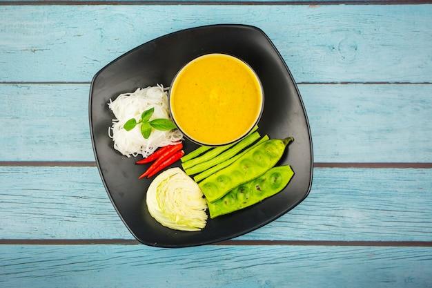 Vista superior macarrão de arroz em molho de caril de peixe com legumes em um fundo azul de madeira