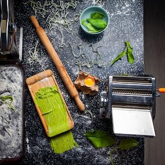 Vista superior macarrão e cozinha ferramentas incluindo rolo com folhas em uma tigela sobre fundo preto texturizado.