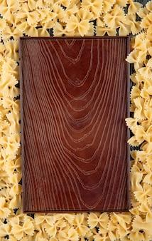 Vista superior macarrão farfalle com espaço de cópia em fundo preto de madeira