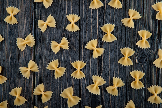 Vista superior macarrão farfalle em fundo preto de madeira