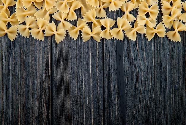 Vista superior macarrão farfalle na parte superior com espaço de cópia no fundo preto de madeira