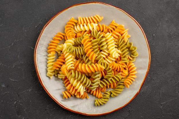 Vista superior macarrão italiano cozido macarrão espiral incomum dentro de um prato no espaço escuro