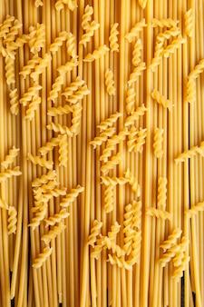 Vista superior macarrão macarrão fusilli com espaguete no fundo. vertical