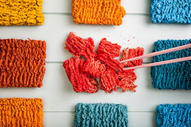 Vista superior macarrão ramen colorido e pauzinhos coloridos