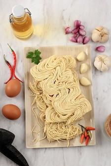 Vista superior macarrão seco asiático amarelo, macarrão indonésio tipicamente chamado bakmi. pronto para cozinhar com especiarias caseiras. na indonésia, popular como mie telor ou bakmi