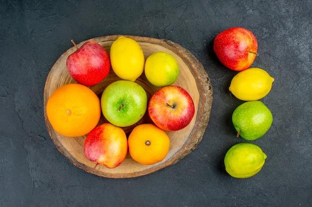 Vista superior, maçãs, limão, laranjas, em, tábua rústica, em, superfície escura
