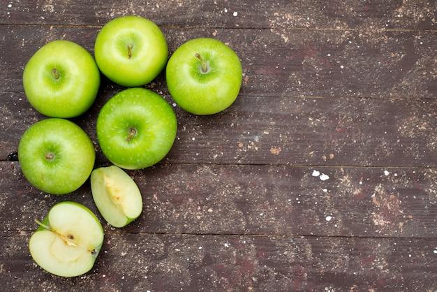 Vista superior maçãs verdes frescas fatiadas e inteiras no escuro